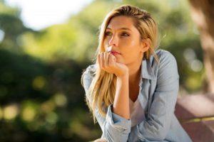 Beautiful, thoughtful woman sitting alone outdoors