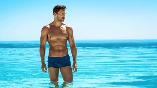 img-blog-Panoramic photo of sexy man posing in swimming pool