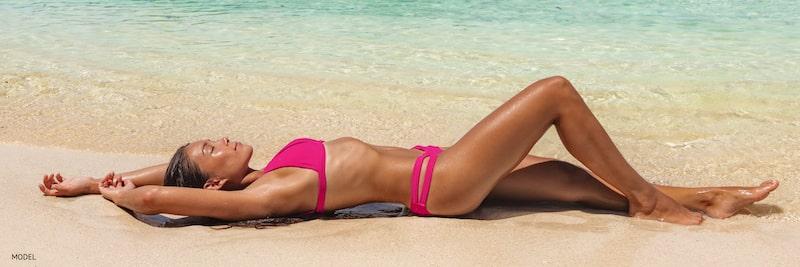 Woman lying back on the sand wearing a pink bikini.