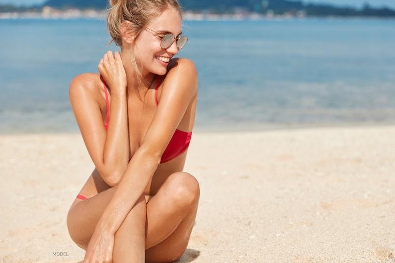 Young woman with smooth legs sitting on beach in pink bikini,