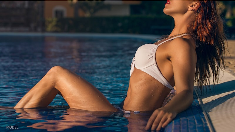 Sexy woman lounging at the edge of a pool.