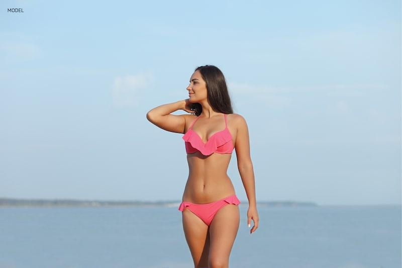 beautiful woman standing on beach in a pink bikini.