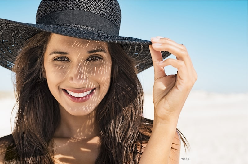 Woman smiling on the beach, wearing a black hat to protect her from the sun.