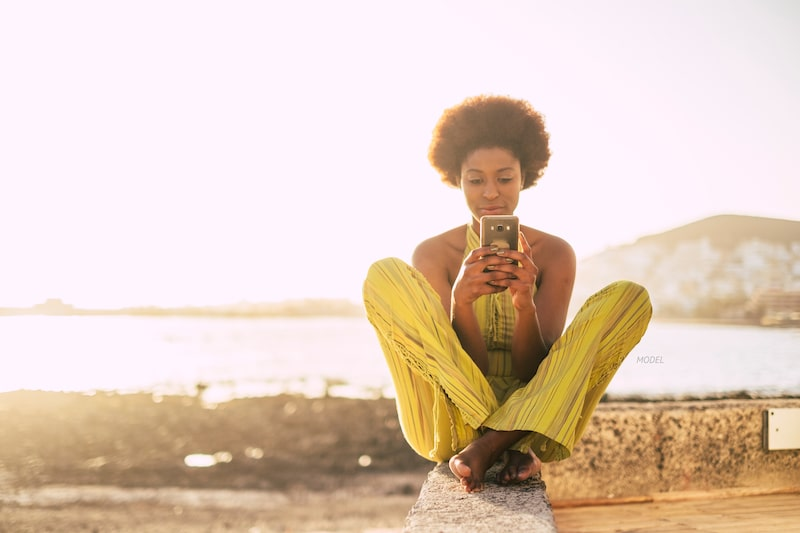 Woman sitting near coast on her cell phone.